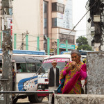 anziana per le vie di Kathmandu consulta il cellulare aspettando il bus